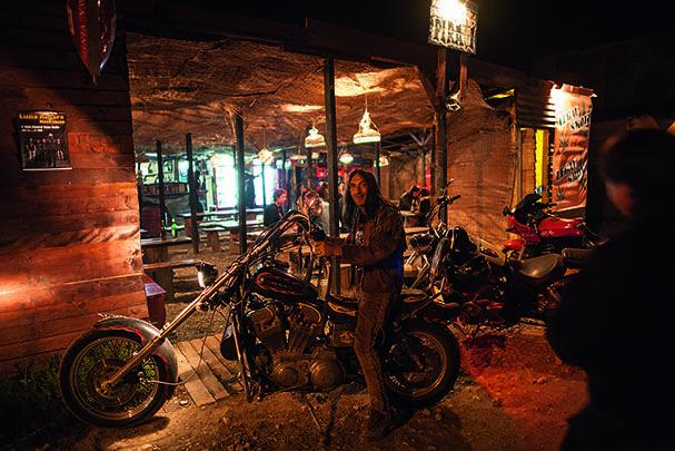 """Un motociclist cu aspect de indian își etalează motorul în fața barului """"La Pirați"""". Locul este o bază a """"Rezistenței"""" în fața schimbărilor din Vamă. Foto: Bogdan Croitoru"""