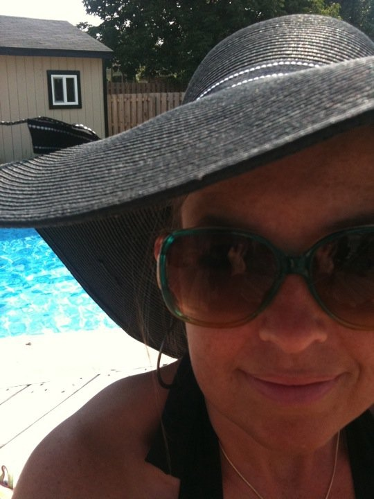 A big floppy hat, bigger sunglasses, and a place by the pool.
