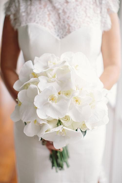 A beautiful all-white orchid bouquet from this destination wedding in Montego Bay, Jamaica. | Brides.com