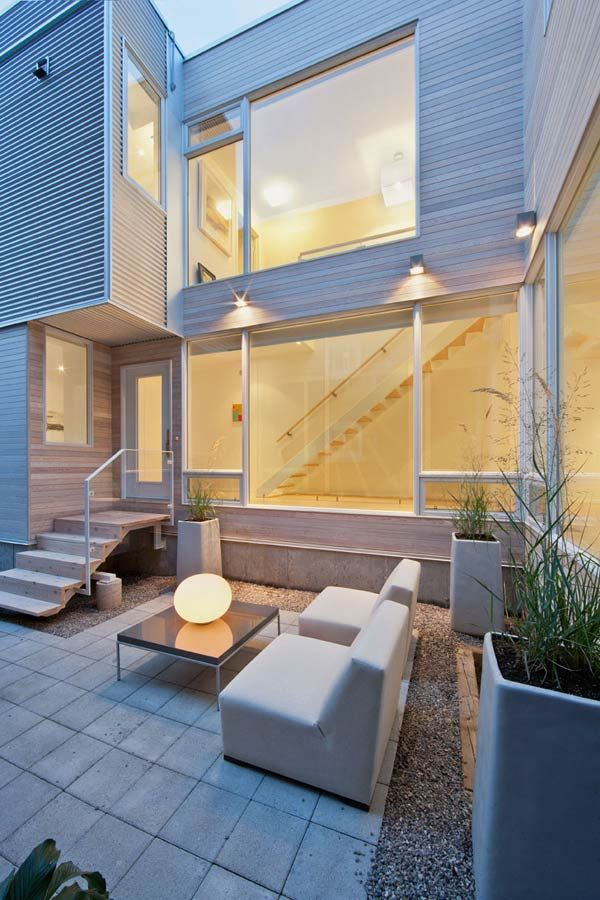 Framed by the large windows and visible from both levels, a chic courtyard and outdoor entertaining area offers alfresco living space that's simple and private, and echoes the contemporary flair of the indoors. Few and fine furnishings make this a space to be enjoyed as much as the interiors.