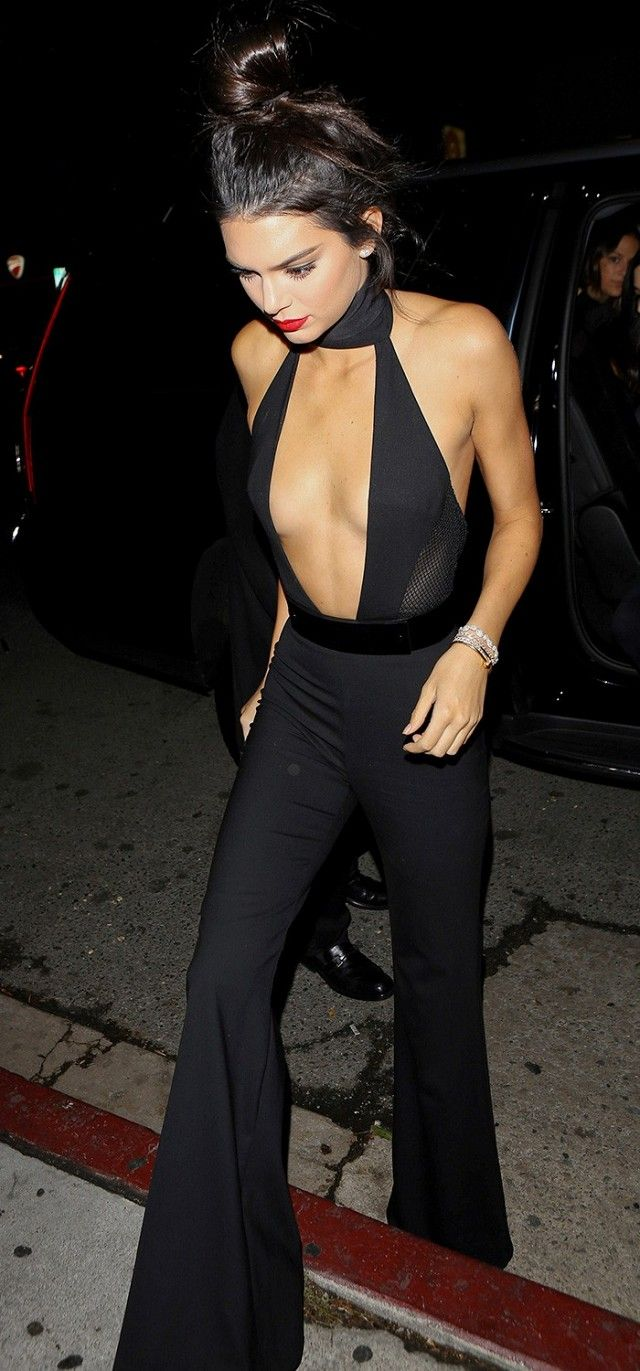 Kendall Jenner wears a plunging black choker top with wide leg trousers and red lipstick. | @andwhatelse