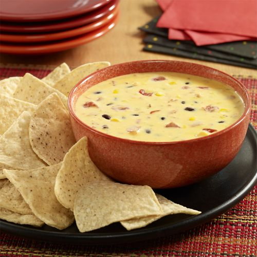 Queso recipe made with Ro*Tel zesty tomatoes and the colorful addition of black beans and corn.  Velveeta is a brand of Kraft Foods Inc.