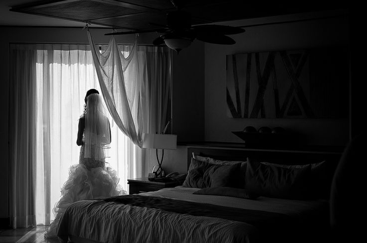 bride looking out of bedroom sliding door black & white