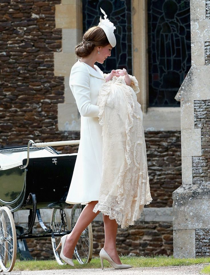 Kate holds her baby daughter Princess Charlotte in her arms as she takes the little girl, dressed in the traditional royal christening gown, into church: