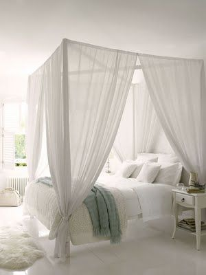 4 Poster Bed with canopy. Love how they keep such a large bed looking light and airy with the sheer white curtains. So romantic!