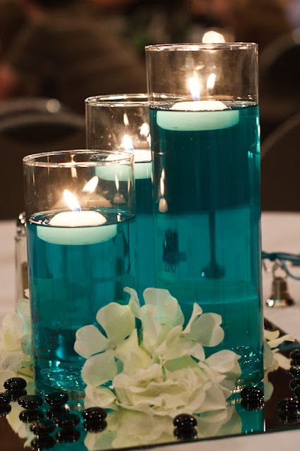 "Centerpieces from our wedding. A little bit of food color & water with some floating candles. Cylinders from dollar store. I like that we can bring in the ""tiffany blue"" color with the orange flowers and white candles"