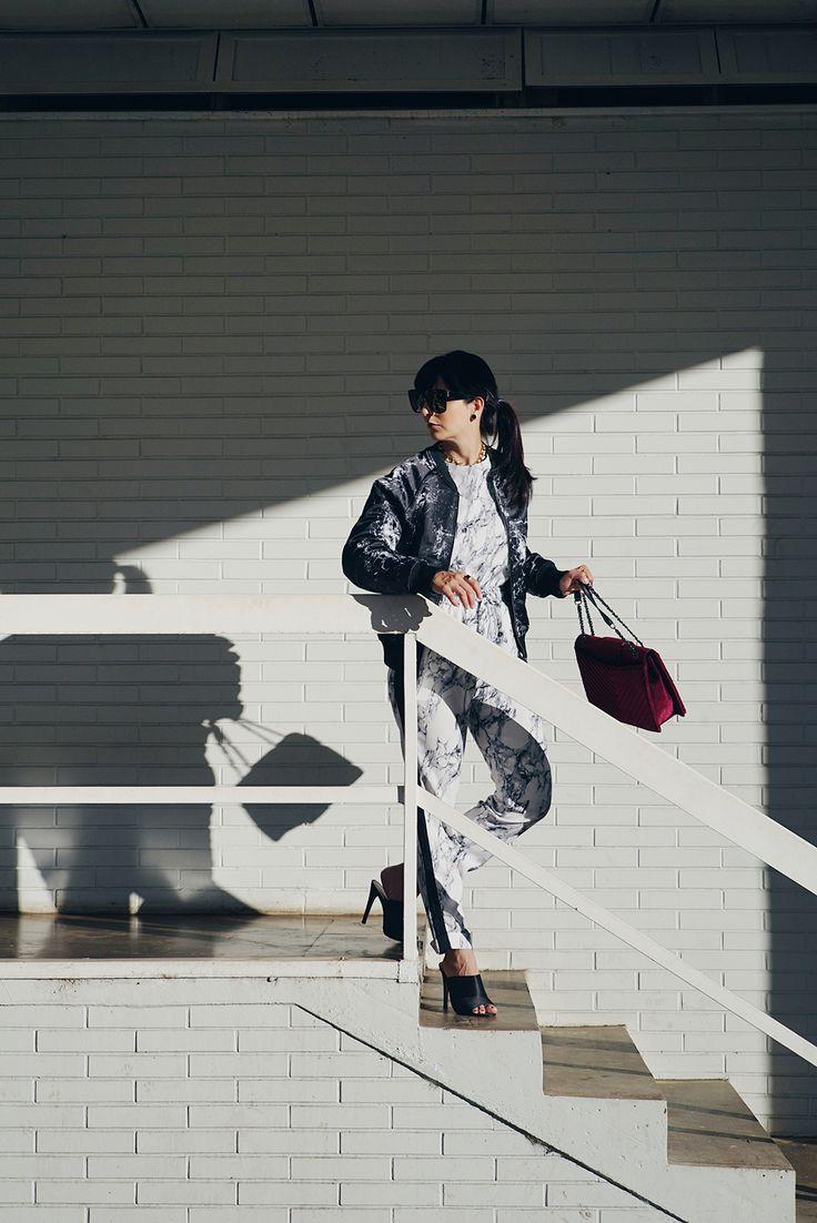 Look urbano da Dani Noce com calça e blusa estampada. bomber jacket, bolsa vermelha de veludo e sapato de salto