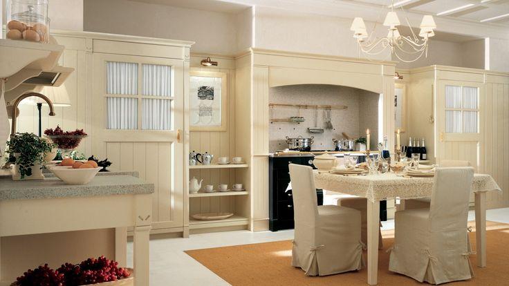 Cucina in stile country chic, finitura Bianco Burro. Tavolo English Mood con sedie Banon rivestite in tessuto.