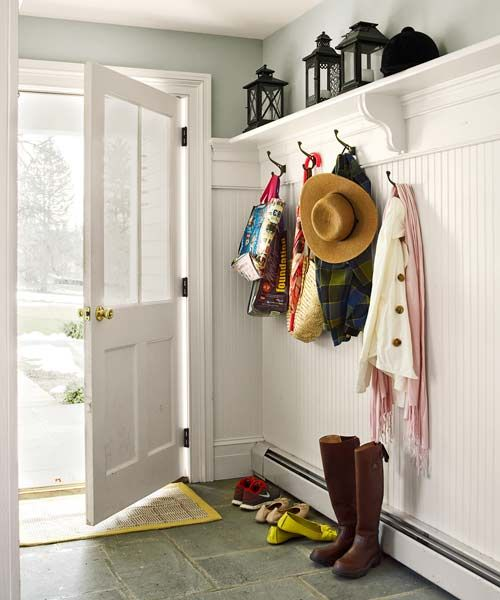 A minimalist mudroom, with boot-friendly blue-stone floor and hooks and shelf for coats and hats, channels guests, kids, and pets alike toward a room-for-all kitchen. | Photo: Tria Giovan | thisoldhouse.com
