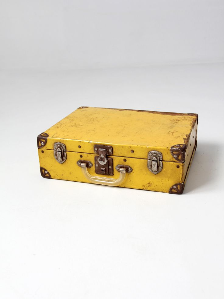 circa 1940s - 1950s This is a small yellow suitcase. The yellow metal case features silver tone corners and hardware. It has a clear plastic handle, and opens to an aged white paper lined interior. -