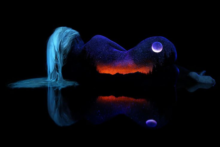 The scene is painted directly on the skin using fluorescent materials and photographed under black light. The model is laying in water to create the lake reflection.