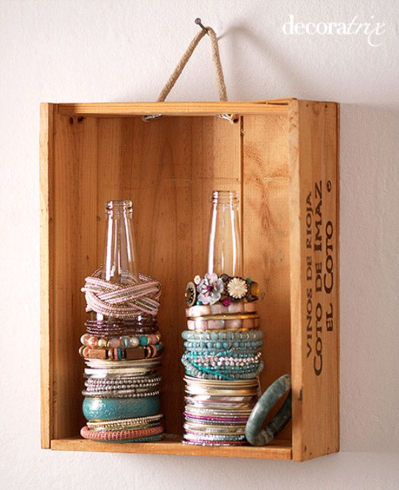 Place 2 recycled bottles in a wooden crate and use as a cool bracelet holder. Hang it on the wall. Simple and functional