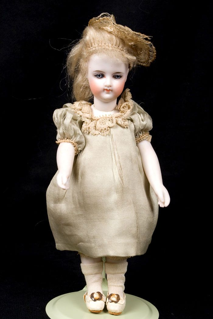 7 and 1/2 inch of perfection and beauty is this large French all bisque doll, circa 1860's. She is all original: dress, underwear, shoes, socks hat , wig and cork pate! The doll has bare feet, which is also a rarity. Her face is unbelievably gorgeous, just like early French Fashion dolls' face, so define with a hint of Mona Lisa smile. Possibly manufactured by Bru!