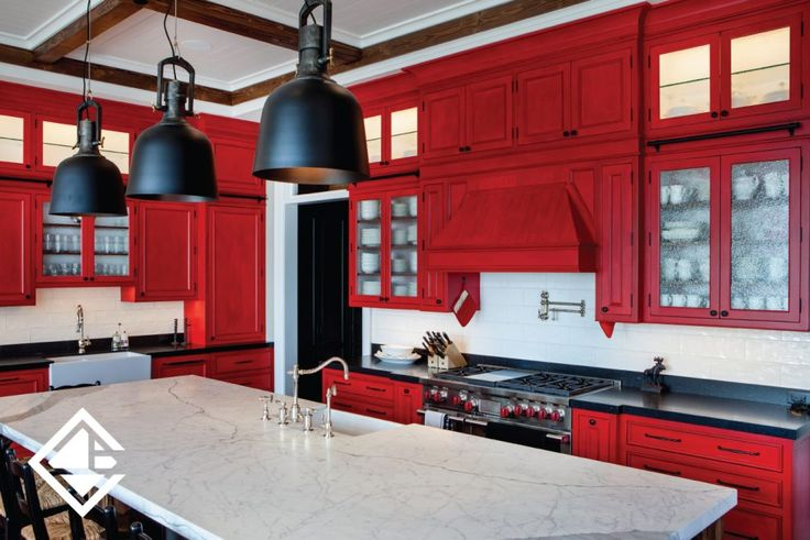 This large open kitchen gives it a rustic/cottage feel. Love the large countertop with the beautiful red custom made cabinetry.