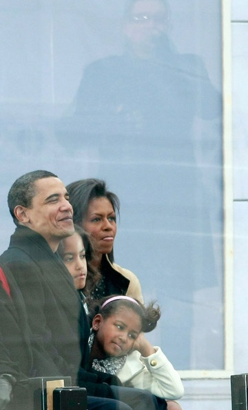 """Bono is reflected in glass as President-elect Barack Obama (L) and his wife Michelle Obama (R) and their daughters Malia Obama (2L) and Sasha Obama watch the musical group U2 perform during """"We Are One: The Obama Inaugural Celebration At The Lincoln Memorial"""" January 18, 2009 in Washington, DC. The event includes a diverse array of talent featuring both musical performances and historical readings and an appearance by U.S. President-elect Barack Obama."""