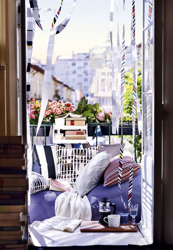 Give a cozy and relaxing look to your balcony by adding soft furniture, green plants and colorfull pillows and plaid blankets.