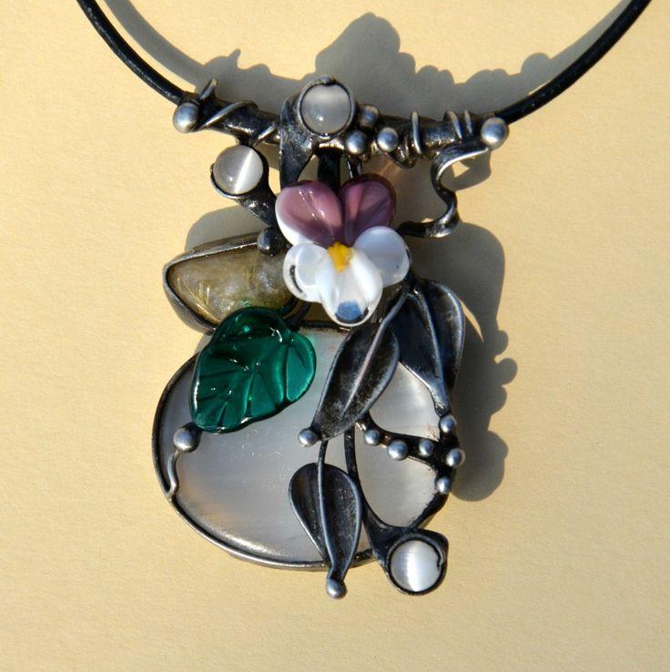 """Maceška+-+selenit,+vinutá+perla+Cínovaný+šperk+je+vytvořen+zvelkého+oválnéhoselenitu+s+krásným+matným+perleťovým+leskem.+Právě+od+jeho+""""měsíčního""""lesku+je+odvozen+i+jeho+název+selenit,+podle+řecké+bohyně+úplňku+Selene.+Je+velký3,5+x3+cm.Dekorací+kamenejsou+originální,+ručně+vinuté+perly+ve+tvarumacešky+azelenéholístečku,+které+se..."""