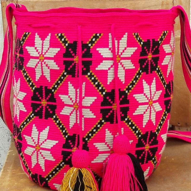 Mochila wayuu diseño floral en tono fucsia.