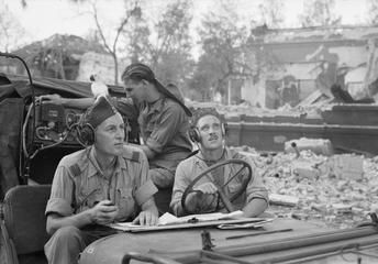 Flight Lieutenant H McDonald DFC (left), Corporal D Mountford (wearing headphones) and Aircraftman D Jull manning a Royal Air Force Visual Control Post in conjunction with 123rd Brigade of the 5th Indian Division operating in Sourabaya (Soerabaja), Java. Aircraftman Jull's pet cockatoo 'Jake' is also on duty. The work of Visual Control Posts was to move forward with the infantry and call in airstrikes by Mosquito or Thunderbolt aircraft on positions held by Indonesian rebels.
