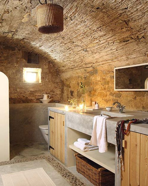 In the master bathroom original stone walls are combined with polished concrete structures.