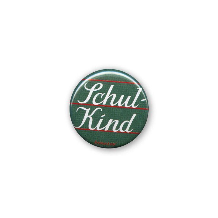 """Buttons sind immer in Mode. Ob Basecap, Jeansjacke oder Schultasche: Dieser Button von krima&isa peppt jede Textilie im Handumdrehen auf. Mit der Metallnadel lässt sich der 2,5 cm große Button schnell und sicher befestigen. Diese Ausführung zeigt den Aufdruck """"Schul-Kind"""": ganz stilecht, wie mit Kreide in Schönschrift auf eine grüne Tafel gemalt."""