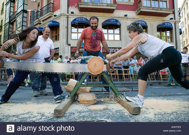 Download this stock image: Female competitors in log sawing contest during Basque Strong Man games in Bilbao northern Spain - AHHYE5 from Alamy's library of millions of high resolution stock photos, illustrations and vectors.