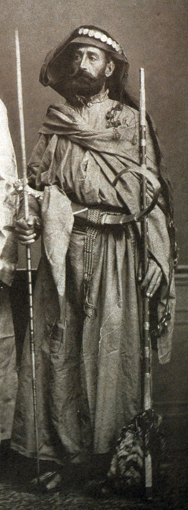 """Resident of Djèaddèlè (Ottoman Mecca), holding a spear and rifle, with a jambiya dagger in his belt. From:Les costumes populaires de la Turquie en 1873, 74 photographic plates by Pascal Sebah, published by the Imperial Ottoman Commission for the """"Exposition Universelle"""" of Vienna in 1873."""