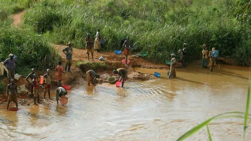Small scale miners working the river bank for gold in the Democratic Republic of Congo. DRC - miners panning for gold.