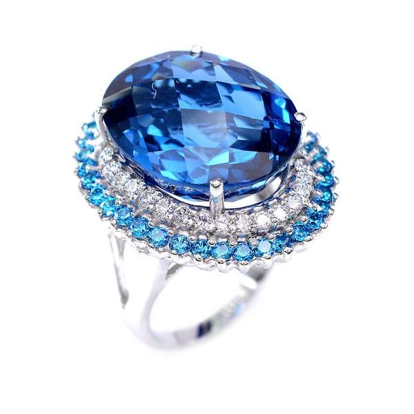 A vintage 27.3CT Oval Cut Swiss Blue Topazwith round cut white & blue sapphire accents halo. This is a gorgeous ring!! 14K whitegold/ sterling silver 27.