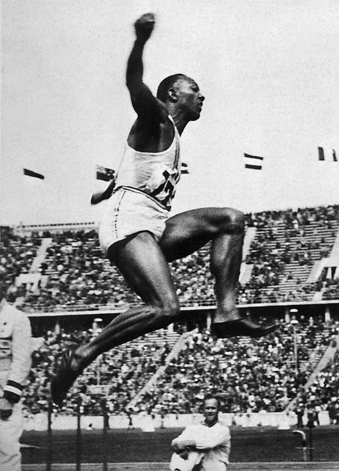 "US champion ""Jesse"" (James Cleveland) Owens is airborne during the long jump event, that he won, 09 August 1936 during Olympic Games in Berlin. Grandson of a slave and legendary athlete, ""Jesse"" Owens established 6 world records in 1935. Jesse Owens retained his 100m world record for 20 years and his long jump world record for 25 years (until 1960). Photo CORR/AFP/Getty Images"