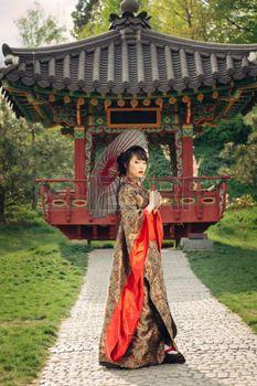kimono japonais: Belle femme asiatique marchant dans le jardin et en kimono traditionnel japonais et parapluie rouge Banque d