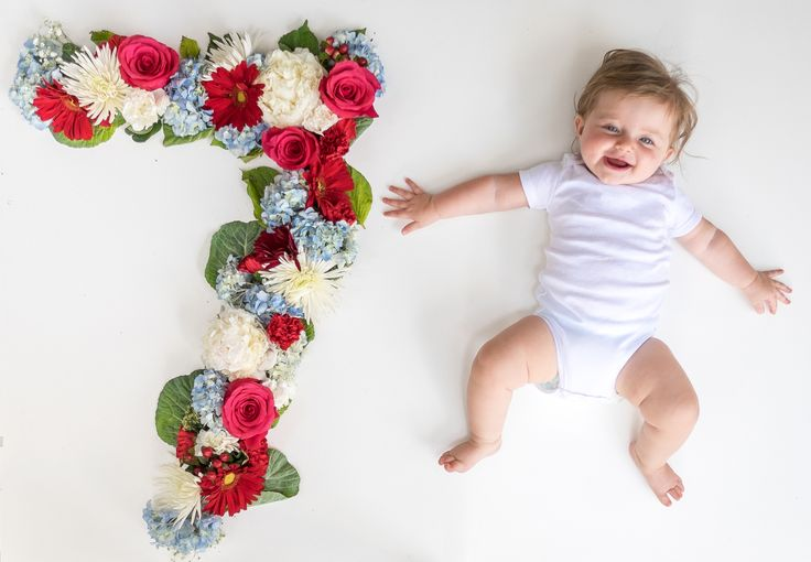 Baby girl monthly pictures. Fresh flowers. Seven months old.