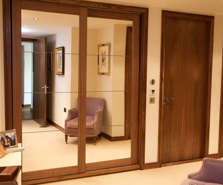 Fitted wardrobes in walnut with mirrored panels