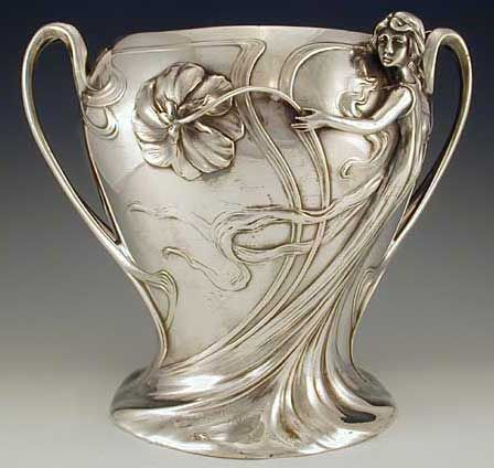 Manufacturer	WMF  Designer	  Description	Silver Plate on pewter champagne bucket with figural maiden Art Nouveau decoration  Country of Manufacture	Germany  Date	1906