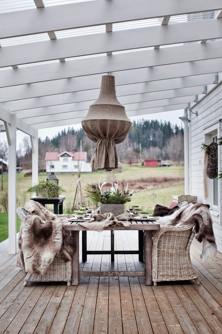 White washed beams for porch roof with big table and wicker chairs