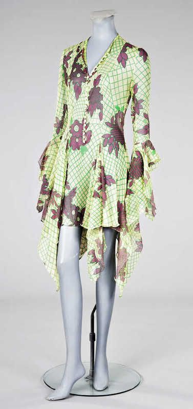 An Ossie Clark/Celia Birtwell printed chiffon twenties inspired dress, circa 1969, printed Ossie label size 12, printed with a green lattice and purple flowers on a primrose chiffon ground, button fronted with handkerchief flounces to cufffs and hem.