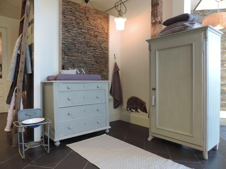 Rustieke babykamer bestaande uit een lichtgrijze kast en commode, mooi gestyled met aubergine accessoires. www.nieuwedromen.nl