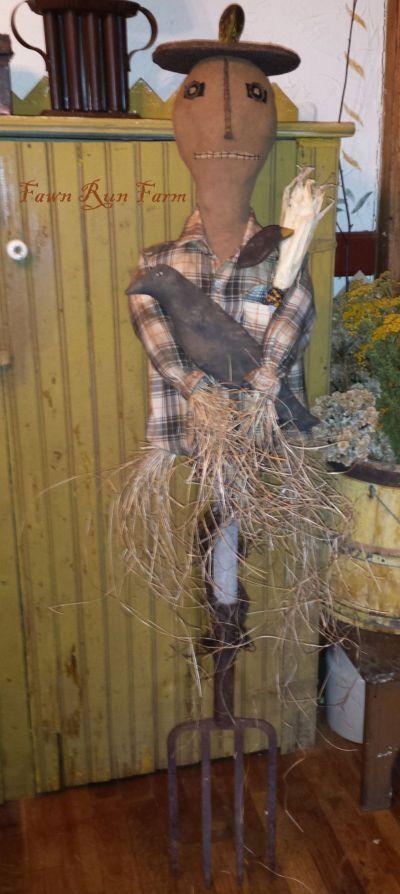 Pumpkin head scarecrow on old potato fork!