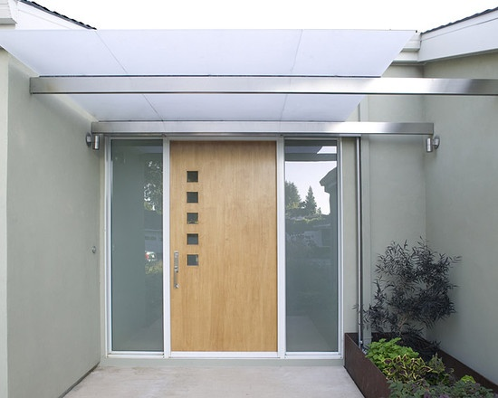 This contemporary front door design features five square windows in vertical row with a smooth, wooden base.