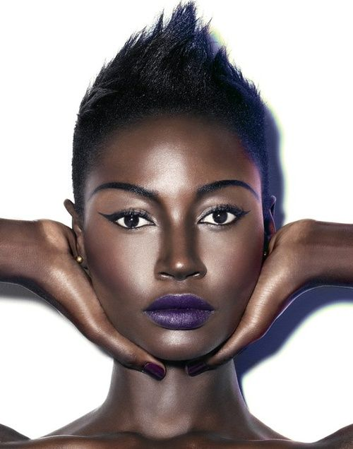 purple lipstick paired with dramatic winged eyeliner, plum blush and bold eyebrows.