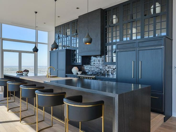 Contemporary black kitchen features three Tom Dixon Beat Light Pendants illuminating a long, black island with waterfall countertop fitted with a gold sink and a gold gooseneck faucet lined with gold and black counter stools, Arteriors Black Calvin Barstools.