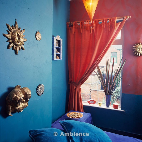 Orange Curtain At Window In Turquoise And Pink Bedroom With Gilt Celestial Motifs On Wall Above