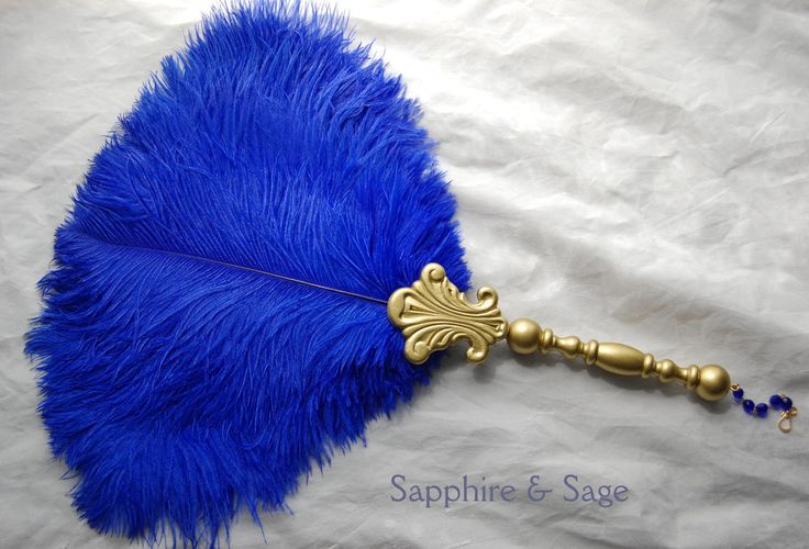 "Elspeth Renaissance Feather Fanwww.sapphireandsage.com Bold and beautiful, this feather fan design is as regal, yet simplistic.  This is the design we offer that most closely replicated Renaissance-era portrait examples of feather fans used by royals during that time period.  Your custom-made wooden handle has the option to be finished with a length of coordinating ribbon or a matching glass beaded chain for hanging, in the artist's color choice.  Approximately 13-16"" wide in size."
