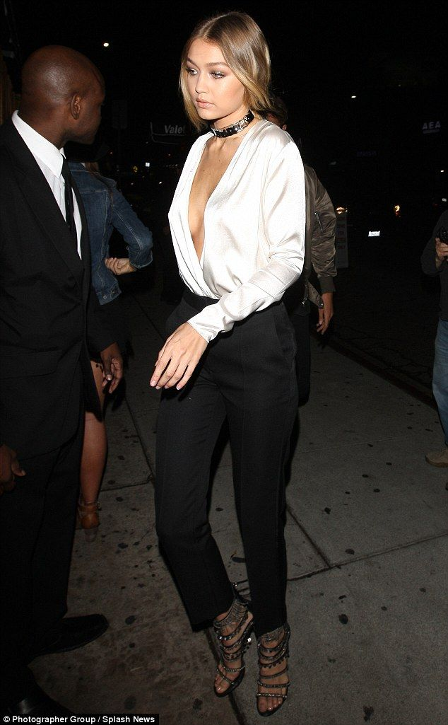Kopykat style: Gigi Hadid somewhat mimicked birthday girl Kendall Jenner's style by baring her cleavage in a plunging silk top as she joined in the celebrations on Monday evening