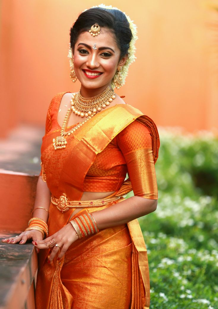 South Indian bride. Gold Indian bridal jewelry.Temple jewelry. Jhumkis. Orange silk kanchipuram sari.Braid with fresh jasmine flowers. .