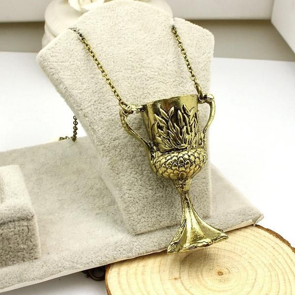 An amazing replica of Helga Hufflepuff's Cup, one of the seven horcruxes in Harry Potter! The antique gold cup features the Hufflepuff badger on the front. The cup itself measures about 5.3cm tall, 3.