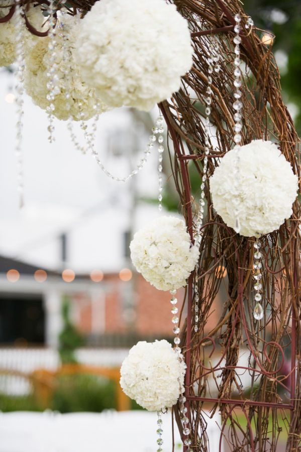 #whiteflower balls decorate this ceremony arch. Photo by Aislinn Kate Photography