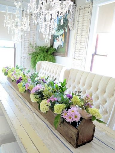 This space makes me happy! The rustic wooden trough filled with fresh blooms is just gorgeous! And the tufted benches and crystal chandeliers? Heaven.