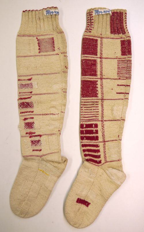 Darning samplers in shape of stockings, one the left stocking even the cast-on edge has been repaired