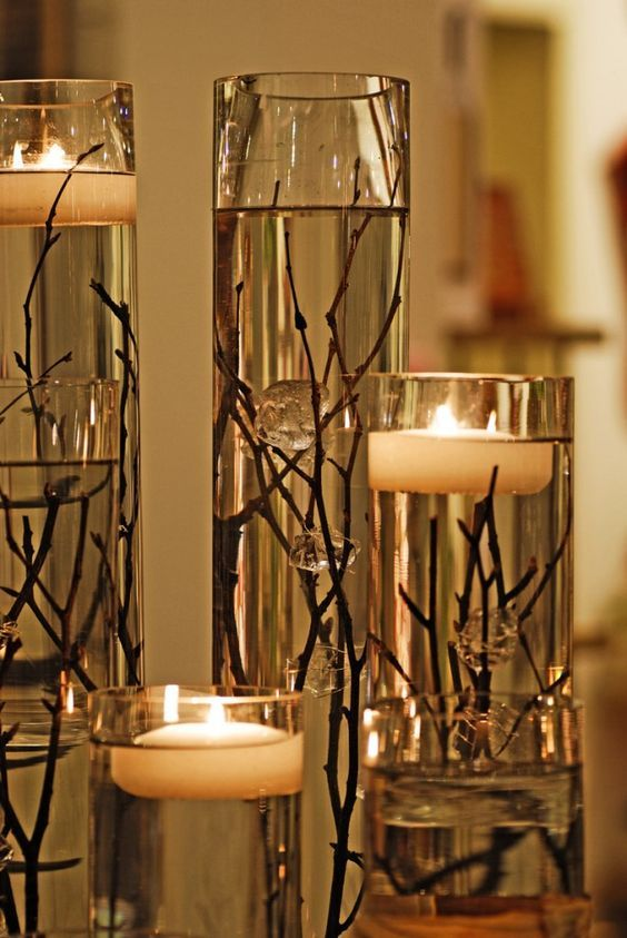 Another great idea for an outdoor evening wedding reception.  Least expensive way to make these would be to buy the various height cylinder vases by the case, artificial twigs with buds in bulk and disk candles in bulk from Internet dealers.  Shop around and compare prices for the best deals.